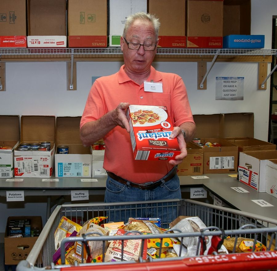 Vietnam-era Army veteran Dan Callender of Hoffman Estates looks for an expiration date on a donated food item as he volunteers at the Schaumburg Township Food Pantry.