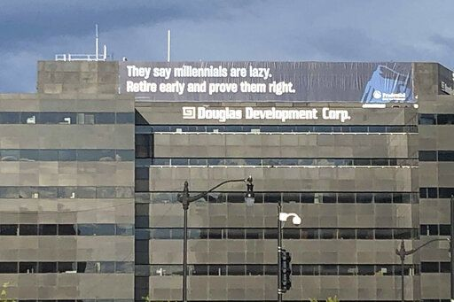 In this June 13, 2019 photo, a retirement advertisement sign is shown on a building in Washington.  Nearly one-quarter of Americans say they never plan to retire, according to a poll that suggests a disconnection between individuals' retirement plans and the realities of aging in the workforce.