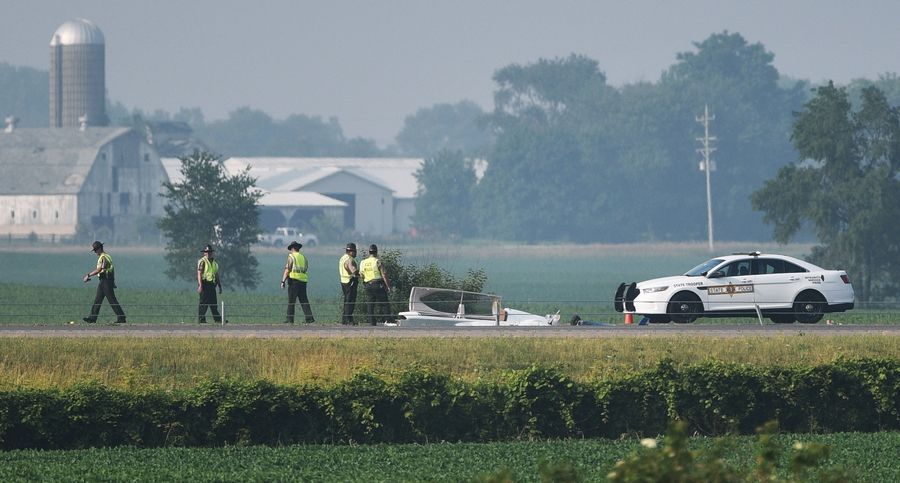 Illinois State Police troopers investigate the scene where a small plane crashed Monday afternoon on the Reagan Memorial Tollway near Kaneville.