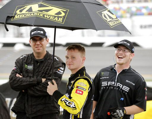 Justin Haley, center, waits on pit road in the rain with crew members after the NASCAR Cup Series auto race was stopped because of weather at Daytona International Speedway, Sunday, July 7, 2019, in Daytona Beach, Fla. Haley was declared the winner a short time later.
