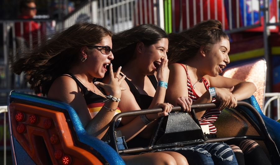 From left, Crystal Retana, Joselin Castillo and her sister Leslie Castillo enjoy a ride Wednesday during the Glendale Heights Fest in Camera Park.