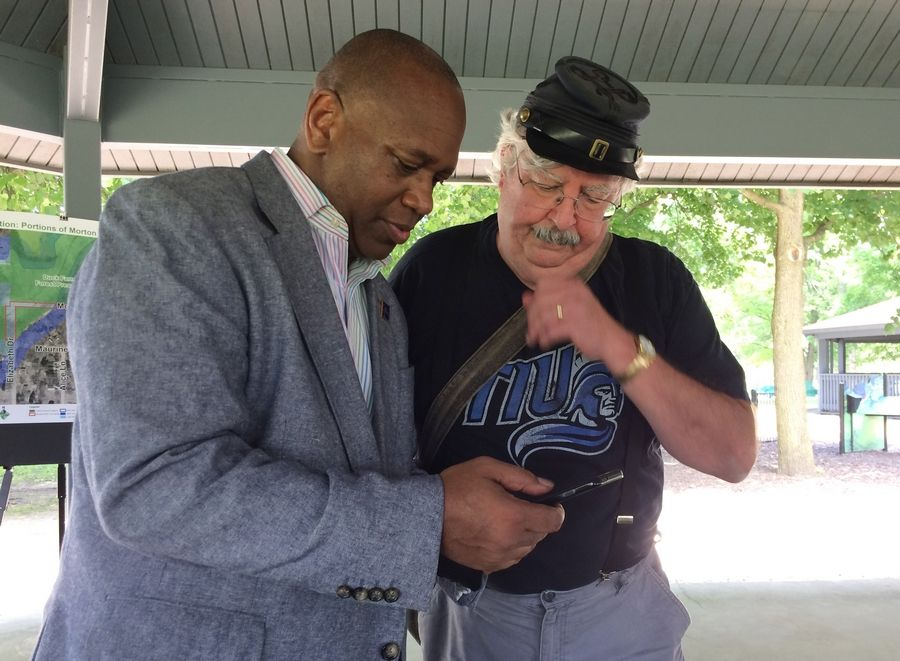 Angelo Kyle, president of the Lake County Forest Preserve District, left, huddles with Steven D. Fratt, a professor of history at Trinity International University after a meeting in which the cancellation of Civil War Days was discussed.