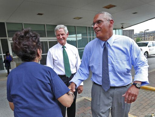 Woody Myers, right, shakes hands with his cousin Elinor Myers Nelson, left, after announcing his bid for governor, Wednesday, July 10, 2019, at the old Wishard Emergency Department where he once worked as a doctor in Indianapolis. Former U.S. Rep. Baron Hill, center, introduced Myers at the event. The Democrat is launching a campaign aimed at unseating Republican Eric Holcomb from the Indiana governor's office next year. (Kelly Wilkinson/The Indianapolis Star via AP)