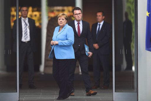 German Chancellor Angela Merkel, center, waits for the arrival of the Prime Minister of Finland Antti Rinne for talks at the chancellery in Berlin, Wednesday, July 10, 2019.