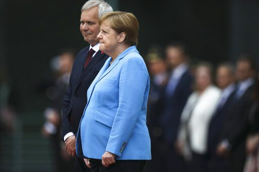 German Chancellor Angela Merkel, right, and Prime Minister of Finland Antti Rinne listen to the national anthems at the chancellery in Berlin, Germany, Wednesday, July 10, 2019. Merkel's body shook visibly as she stood alongside the Finnish prime minister and listen to the national anthems during the welcoming ceremony at the chancellery.