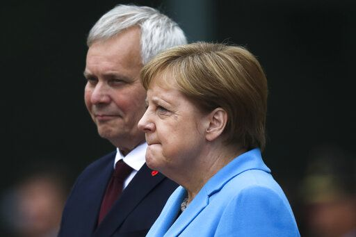 German Chancellor Angela Merkel and Prime Minister of Finland Antti Rinne listen to the national anthems during the welcoming ceremony at the chancellery in Berlin, Germany, Wednesday, July 10, 2019.