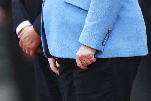 The hands of German Chancellor Angela Merkel, right, and Finland's Antti Rinne as they listen to the national anthems at the chancellery in Berlin, Wednesday, July 10, 2019. Merkel's body shook visibly as she stood alongside the Finnish prime minister and listen to the national anthems during the welcoming ceremony at the chancellery.