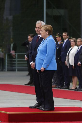 German Chancellor Angela Merkel, right, and Prime Minister of Finland Antti Rinne listen to the national anthems at the chancellery in Berlin, Wednesday, July 10, 2019. Merkel's body shook visibly as she stood alongside the Finnish prime minister and listen to the national anthems during the welcoming ceremony at the chancellery.