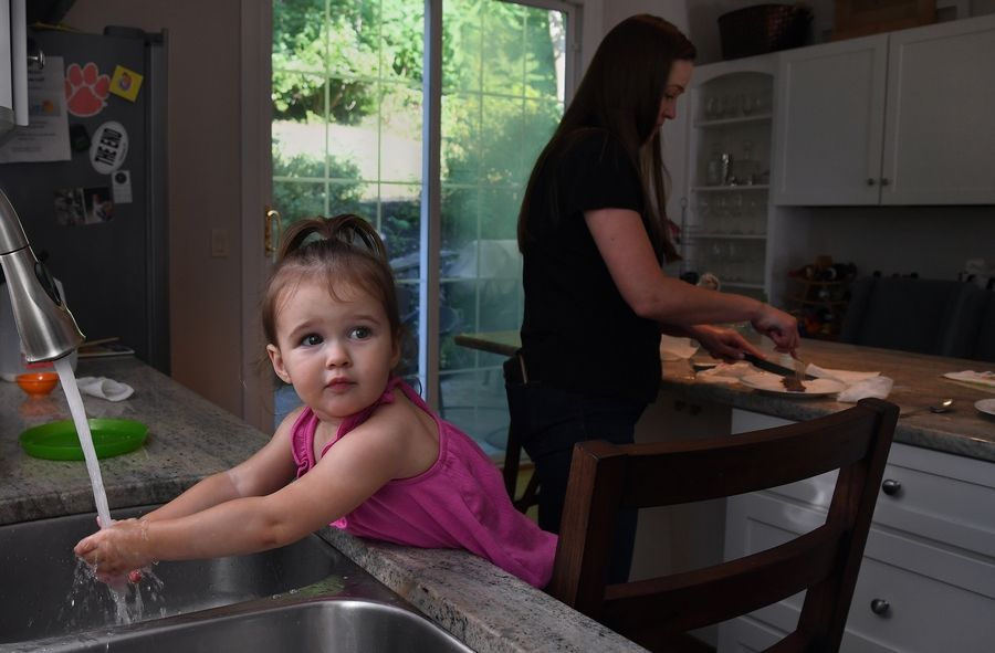 Lauren Sullivan makes dinner as Daryn washes her hands at their home in McLean, Va. on July 5.