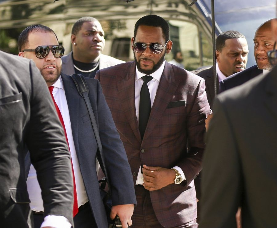 FILE -- In this June 26, 2019, file photo, R&B singer R. Kelly, center, arrives at the Leighton Criminal Court building for an arraignment on sex-related felonies in Chicago. R. Kelly, already facing sexual abuse charges brought by Illinois prosecutors, was arrested in Chicago Thursday, July 11, 2019 on a federal grand jury indictment listing 13 counts including sex crimes and obstruction of justice.