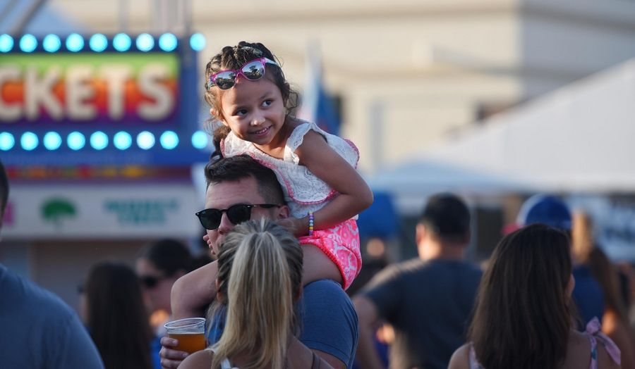 Daniella Villegas, 5, sits on her dad Nick's shoulders at the first night of Itasca Fest Thursday. They were watching her sister Iylah, 7, ride a midway ride with her mother Jordan. They are from Roselle.