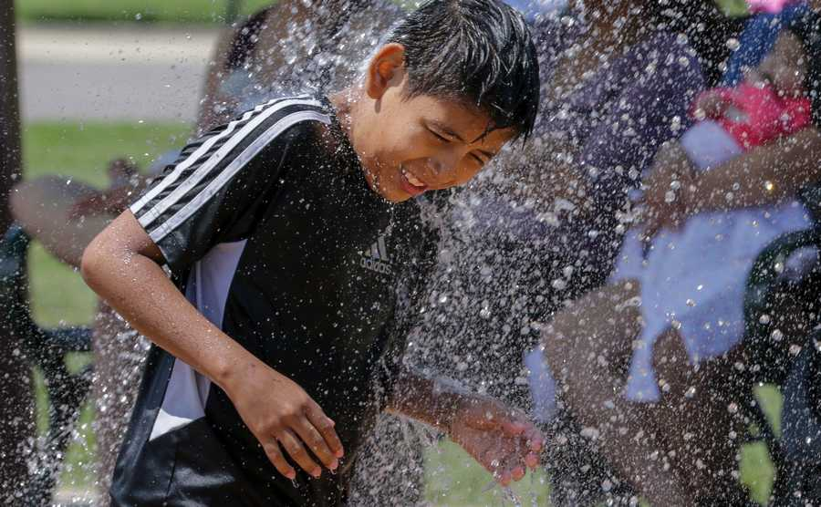 Allan Ramos, 10, cools off at the Phillips Park Splash Pad in Aurora.