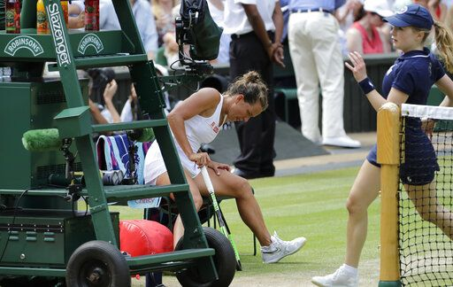 Czech Republic's Barbora Strycova holds her thigh as she sits down in a change of ends break as she plays United States' Serena Williams in a Women's semifinal singles match on day ten of the Wimbledon Tennis Championships in London, Thursday, July 11, 2019.