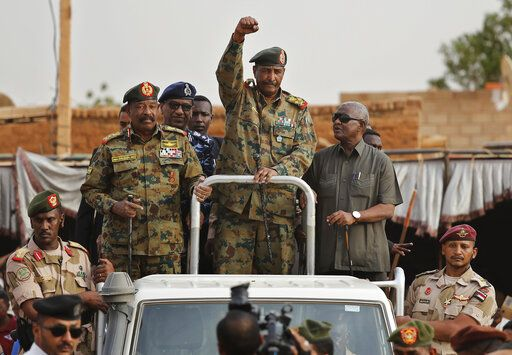 FILE - In this Saturday, June 29, 2019, file photo, Sudanese Gen. Abdel-Fattah Burhan, head of the military council, waves to his supporters upon his arrival to attend a military-backed rally in Omdurman district, west of Khartoum, Sudan. The power-sharing agreement reached between Sudan's military and pro-democracy protesters last week came after the United States and its Arab allies applied intense pressure on both sides amid fears a prolonged crisis could tip the country into civil war, activists and officials said.