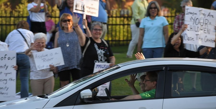 "Drivers express their support to those in a ""Lights for Liberty"" vigil along Northwest Highway in Arlington Heights to protest the conditions faced by migrants near the southern U.S. border."