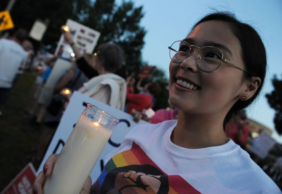 "Emma Serikaku of Palatine holds a candle at a ""Lights for Liberty"" vigil Friday night along Northwest Highway in Arlington Heights to protest the conditions faced by migrants near the southern U.S. border."