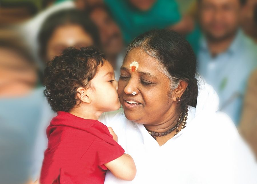 Humanitarian Amma embraces young visitor.