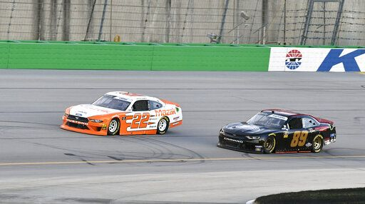 Austin Cindric (22) tries to fight off the challenge from Morgan Shepherd (89) during the NASCAR Xfinity Series auto race at Kentucky Speedway in Sparta, Ky., Friday, July 12, 2019.