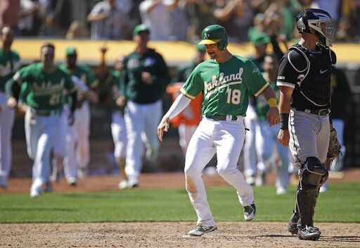 Oakland Athletics' Chad Pinder (18) scored the game winning run behind Chicago White Sox catcher James McCann in the ninth inning of a baseball game Sunday, July 14, 2019, in Oakland, Calif. Pinder scored on a throwing error by Chicago's Jose Rondon.