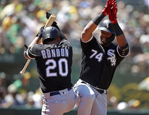 Chicago White Sox Eloy Jimenez, right, celebrates with Jose Rondon, left, after hitting a homerun off Oakland Athletics' Brett Anderson in the seventh inning of a baseball game Sunday, July 14, 2019, in Oakland, Calif.