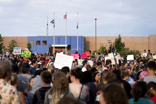 In this Friday, July 12, 2019, photo, hundreds of protesters assemble for a march at the GEO facility in Aurora, Colo. Police say they will be reviewing any available video to help them identity protesters who trespassed and pulled down the American flag in front of an immigration detention center in suburban Denver, tried to burn it and replaced it with a Mexican flag. (Philip B. Poston/The Aurora Sentinel via AP)