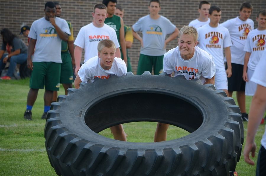 St. Charles East High School linemen compete in the tractor-tire relay at the 2014 Battle of the Big Butts at West Aurora High School.