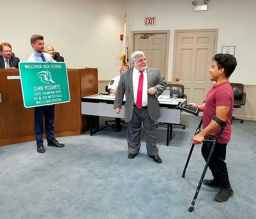State champion athlete Juan Rodarte, right, receives a plaque from Wauconda Mayor Lincoln Knight at village hall Monday. Village Administrator Kevin Timony, left, shows off a street sign that will honor Rodarte.