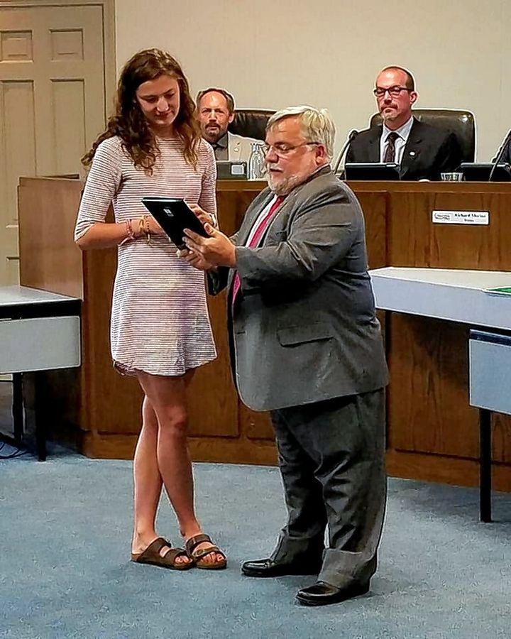 State champion athlete Grace Daun receives a plaque from Wauconda Mayor Lincoln Knight at village hall Monday.