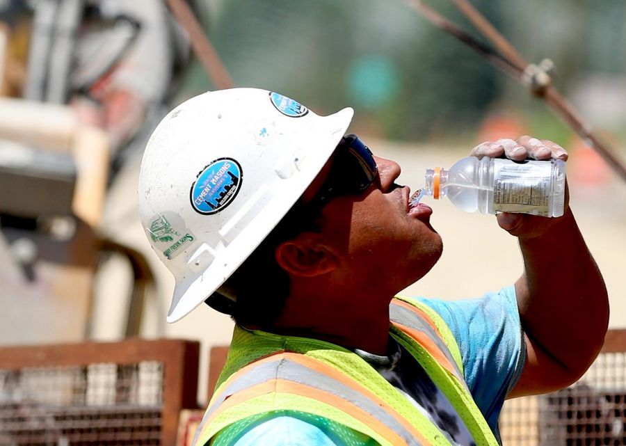 Ivan Gonzalez of Hanover Park takes a drink of cold water as he works with a crew from Plote Construction resurfacing Randall Road on Monday in Lake in the Hills.