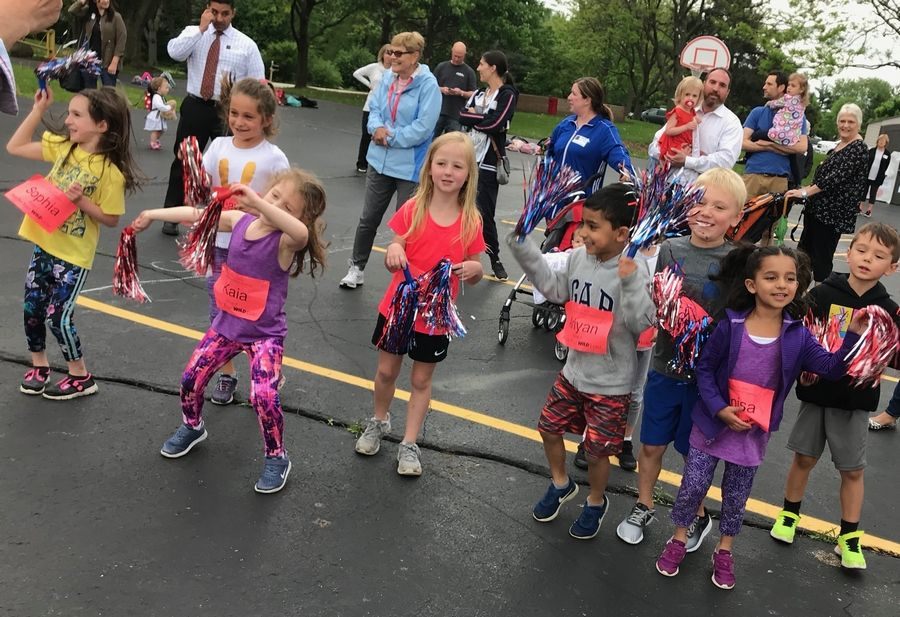Holy Family Catholic Academy kindergarten students and supporters cheer on classmates in the Run For Your Wild Life fundraising event. After learning about endangered animals, the students raised almost $4,000 to support the Wildlife Conservation Network.