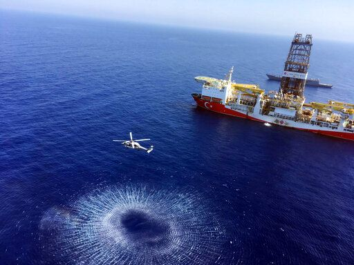 In this Tuesday, July 9, 2019 photo, a helicopter flies near Turkey's drilling ship, 'Fatih' dispatched towards the eastern Mediterranean, near Cyprus. Turkish officials say the drillships Fatih and Yavuz will drill for gas, which has prompted protests from Cyprus.(Turkish Defence Ministry via AP, Pool)