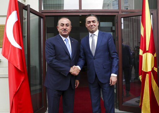 "Turkey's Foreign Minister Mevlut Cavusoglu, left, shakes hands with North Macedonia's Foreign Minister Nikola Dimitrov, right, prior to their meeting, in Skopje, North Macedonia, Tuesday, July 16, 2019. Cavusoglu on Tuesday downplayed as ""worthless"" an initial set of sanctions approved by the European Union against Ankara and vowed to send a new vessel to the eastern Mediterranean to reinforce its efforts to drill for hydrocarbons off the island of Cyprus. EU foreign ministers on Monday approved sanctions against Turkey over its drilling for gas in waters where EU member Cyprus has exclusive economic rights. (Cem Ozdel/Turkish Foreign Ministry via AP, Pool)"