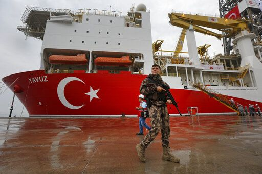 FILE-In this Thursday, June 20, 2019 file photo, a Turkish police officer patrols the dock, backdropped by the drilling ship 'Yavuz' that was dispatched to the Mediterranean, at the port of Dilovasi, outside Istanbul. The Turkish Foreign Ministry said Wednesday, July 10, 2019 it rejects the European Union's statements condemning its efforts to drill for gas in waters off the coast of Cyprus and says the EU cannot be considered an impartial mediator for the divided island. Cyprus says Turkey is encroaching in waters where the country has exclusive economic rights while the European Union warned Turkey of sanctions.