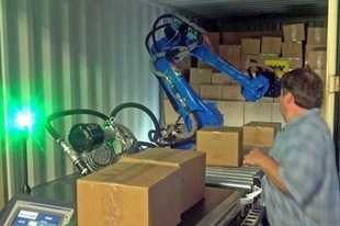 A Wynright employee monitors a robotic freight unloader as it pulls boxes from a trailer onto a conveyor belt at its Elk Grove Village headquarters. The company confirmed Wednesday it will close the headquarters and another suburban facility when it relocates to a new site in Hobart, Indiana, at the end of the year.