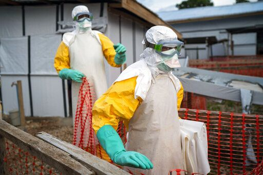 In this photograph taken Saturday July 13, 2019, health workers wearing protective suits take their shift at a treatment center in Beni, Congo DRC. The head of the World Health Organization is convening a meeting of experts Wednesday July 17, 2019 to decide whether the Ebola outbreak should be declared an international emergency after spreading to eastern Congo's biggest city, Goma, this week. More than 1,600 people in eastern Congo have died as the virus has spread in areas too dangerous for health teams to access.