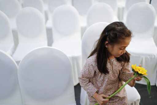 A girl holds a flower as friends and family of victims from Malaysia Airlines Flight MH17 plane crash attend a ceremony marking the fifth anniversary of the tragedy in Kuala Lumpur, Malaysia, Wednesday, July 17, 2019. Five years after a missile blew Malaysia Airlines Flight 17 out of the sky above eastern Ukraine, relatives and friends of those killed gathered Wednesday in Kuala Lumpur and at a Dutch memorial to mark the anniversary.