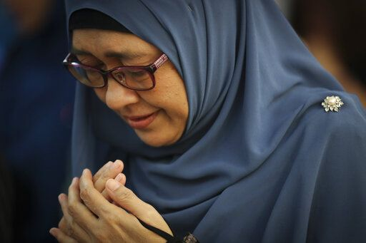 A woman prays as friends and family of victims from Malaysia Airlines Flight MH17 plane crash attend a ceremony marking the fifth anniversary of the tragedy in Kuala Lumpur, Malaysia, Wednesday, July 17, 2019. Five years after a missile blew Malaysia Airlines Flight 17 out of the sky above eastern Ukraine, relatives and friends of those killed gathered Wednesday in Kuala Lumpur and at a Dutch memorial to mark the anniversary.