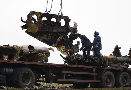 FILE - In this file photo dated Sunday, Nov. 16, 2014, recovery workers in rebel-controlled eastern Ukraine load debris from the crash site of Malaysia Airlines Flight 17, in Hrabove, Ukraine, with recovery operations carried out under the supervision of Dutch investigators and officials from the Organization for Security and Cooperation in Europe.  Five years after a missile blew Malaysia Airlines Flight 17 out of the sky above eastern Ukraine, relatives and friends of those killed will gather Wednesday July 17, 2019, at a Dutch memorial to mark the anniversary.