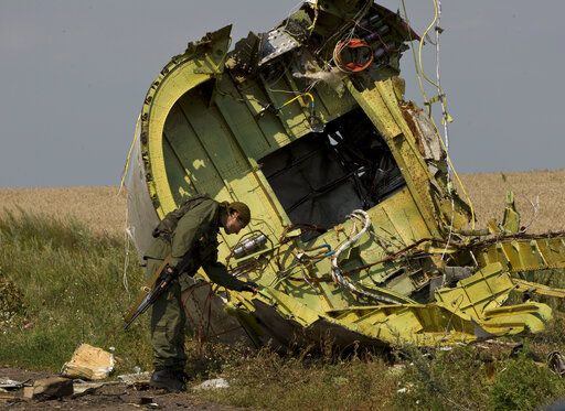 FILE - In this July 22, 2014 file photo, a pro-Russian rebel touches the MH17 wreckage at the crash site of Malaysia Airlines Flight 17, near the village of Hrabove, eastern Ukraine.  Five years after a missile blew Malaysia Airlines Flight 17 out of the sky above eastern Ukraine, relatives and friends of those killed are gathering Wednesday July 17, 2019, at a Dutch memorial to mark the anniversary.