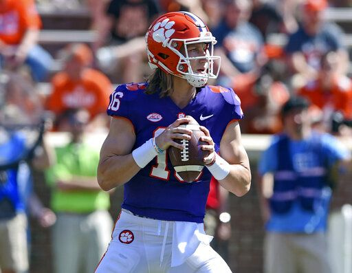 FILE - In this April 6, 2019, file photo, Clemson's Trevor Lawrence drops back to pass during Clemson's annual Orange and White NCAA college football spring scrimmage in Clemson, S.C. Clemson's defense was a big reason why the Tigers won a second national championship in three seasons. Now that unit has massive holes to fill after losing its entire front to the NFL, along with three key linebackers and two members of the secondary _ and that could mean the Tigers have to win shootouts behind quarterback Trevor Lawrence to stay on top.