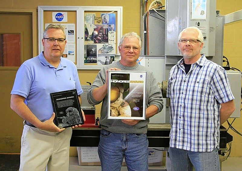 Brothers Mike, Bob and John Cain, third-generation owners of Cain Tubular Products in St. Charles, hold the Honoree Award they received from NASA for their contributions to the J2X rocket engine program.