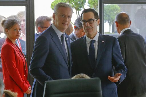 French Finance Minister Bruno Le Maire, left, talks to US Treasury Secretary Steve Mnuchin during a meeting at the G-7 Finance in Chantilly, north of Paris, on Thursday, July 18, 2019.