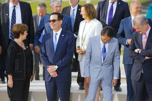 US Treasury Secretary Steve Mnuchin, second left, talks to Chief Executive of the World Bank Kristalina Georgieva, left, next to Japan's Finance Minister Taro Aso, second right, and Bank of France Governor Francois Villeroy de Galhau, right, prior a group photo at the G-7 Finance in Chantilly, north of Paris, on Wednesday, July 17, 2019. The Group of Seven rich democracies' top finance officials gathered Wednesday at a chateau near Paris in search of common ground on the threats posed by digital currencies.