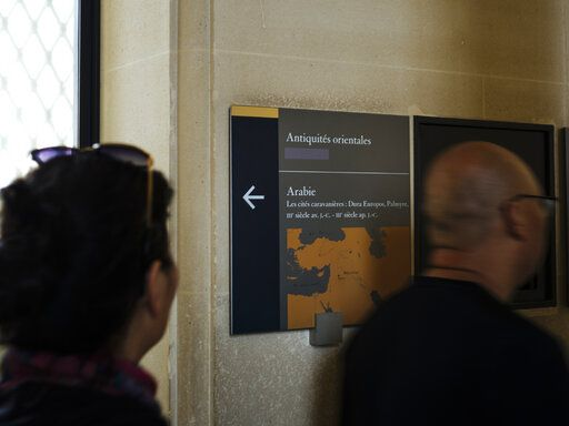 Visiotrs walk past a taped over sign at the Louvre Museum in Paris, France, Wednesday, July 17, 2019. France's Louvre museum has taped over the Sackler name as donors to a wing of the building after protests against the family blamed for the opioid crisis in the United States.