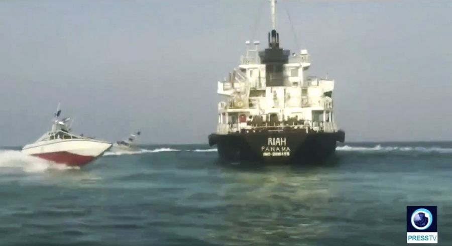 This undated photo provided by Iranian state television's English-language service, Press TV, shows the Panamanian-flagged oil tanker MT Riah surrounded by Iranian Revolutionary Guard vessels. Iran said Thursday, July 18, 2019, that its Revolutionary Guard seized a foreign oil tanker and its crew of 12 for smuggling fuel out of the country. The Riah, which had disappeared off trackers in Iranian territorial waters over the weekend, stopped transmitting its location early Sunday near Iran's Qeshm Island, according to data listed on tracking site Maritime Traffic. (Press TV via AP)