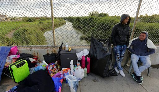 "FILE - In this Nov. 2, 2018, file photo, Yenly Morales,left, and Yenly Herrera, right, immigrants from Cuba seeking asylum in the United States, wait on the Brownsville and Matamoros International Bridge in Matamoros, Mexico. The U.S. government will expand its policy requiring asylum seekers to wait outside the country in one of Mexico's most dangerous cities. According to officials for two congressional Democrats, the Department of Homeland Security says it will implement its ""Migrant Protection Protocols"" in Brownsville, Texas, across the border from Matamoros, Mexico. Matamoros is in Mexico's Tamaulipas state, which the U.S. government warns citizens not to visit due to violence and kidnappings."