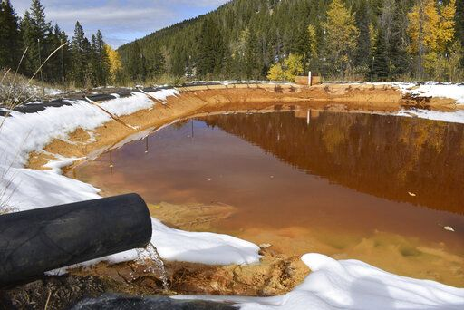 FILE - In this Oct. 12, 2018, file photo, water contaminated with arsenic, lead and zinc flows from a pipe out of the Lee Mountain mine and into a holding pond near Rimini, Mont. An appeals court Friday, July 19, 2019, has sided with the Trump administration after it dropped a proposal that would have required mining companies to prove they have the wherewithal to clean up future pollution.