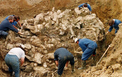 FILE - In this Sept. 18, 1996 file photo, International War Crimes Tribunal investigators clear away soil and debris from dozens of Srebrenica victims buried in a mass grave near the village of Pilica, some 55 kms (32 miles) north east of Tuzla, Boisnia-Herzegovina. The Dutch Supreme Court is ruling Friday July 19, 2019 in a long-running legal battle over whether the Netherlands can be held liable in the deaths of more than 300 Muslim men who were murdered by Bosnian Serb forces during the 1995 Srebrenica massacre..