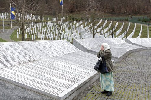 FILE - In this Wednesday, March 20, 2019 file photo, a woman prays at the Potocari memorial center for victims of the Srebrenica genocide, in Potocari, Bosnia and Herzegovina. The Dutch Supreme Court is ruling Friday July 19, 2019 in a long-running legal battle over whether the Netherlands can be held liable in the deaths of more than 300 Muslim men who were murdered by Bosnian Serb forces during the 1995 Srebrenica massacre.