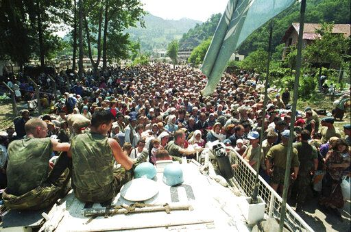 FILE - In this July 13, 1995 file photo, Dutch U.N. peacekeepers sit on top of an armored personnel carrier while Muslim refugees from Srebrenica, eastern Bosnia, gather in the village of Potocari, just north of Srebrenica. The Dutch Supreme Court is ruling Friday July 19, 2019 in a long-running legal battle over whether the Netherlands can be held liable in the deaths of more than 300 Muslim men who were murdered by Bosnian Serb forces during the 1995 Srebrenica massacre.